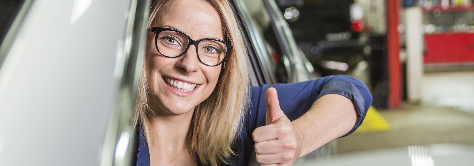 Satisfied customer giving a thumbs up from her vehicle window